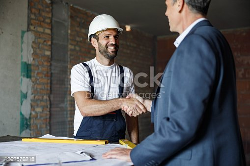 961745166 istock photo Happy worker shaking hands with architect at construction site. 1262576218