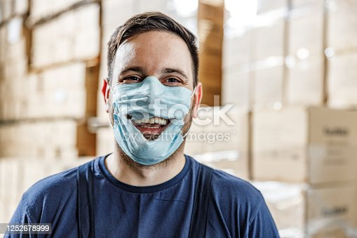 Happy worker wearing torn protective face mask in order to show anti-quarantine protest and looking at camera.