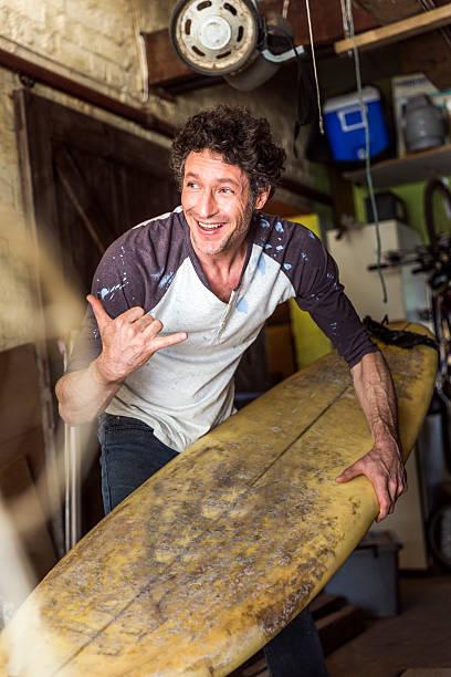 happy worker showing shaka sign while holding surfboard - surf garage bildbanksfoton och bilder