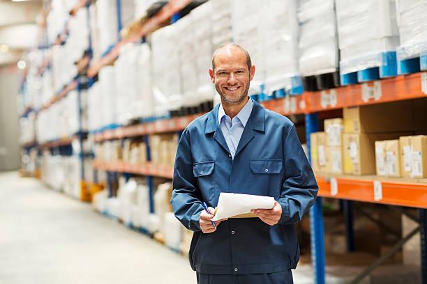 Happy worker standing in warehouse - Photo