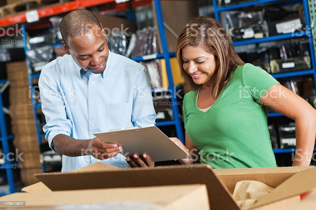Happy workers checking orders in distribution warehouse royalty-free stock photo
