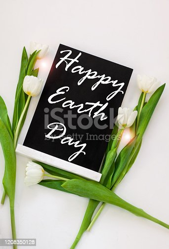 Happy Earth Day April 22 greeting message sign on black chalk board with tulip flowers on white background. World ecology concept card.Saving environment, save clean planet.Blackboard with text,banner
