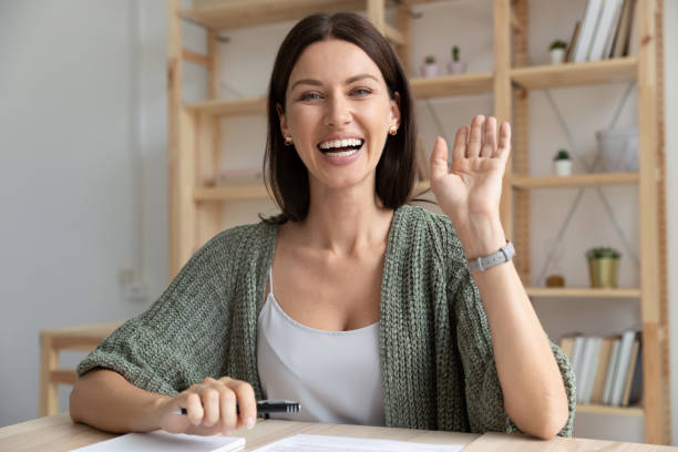 Happy young 30s woman waving hello to camera. Head shot happy young 30s woman sitting at wooden desk, looking at camera, waving hello. Excited businesswoman teacher lecturer recording educational video, greeting students at online workshop. bingo caller stock pictures, royalty-free photos & images
