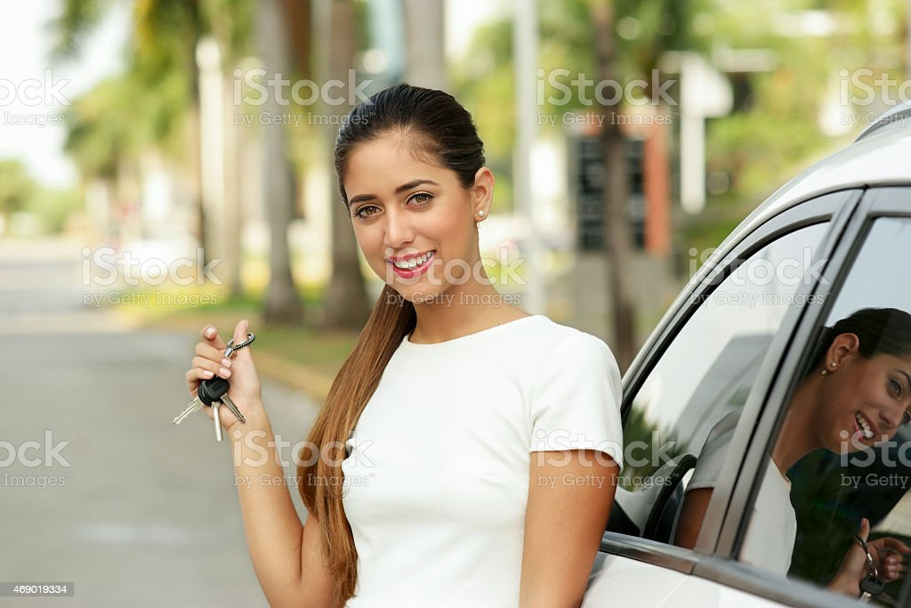 Happy young adult smiling and showing keys of new car stock photo