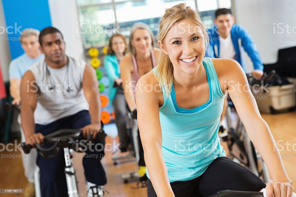 Happy young adult woman leading cycling fitness class royalty-free stock photo