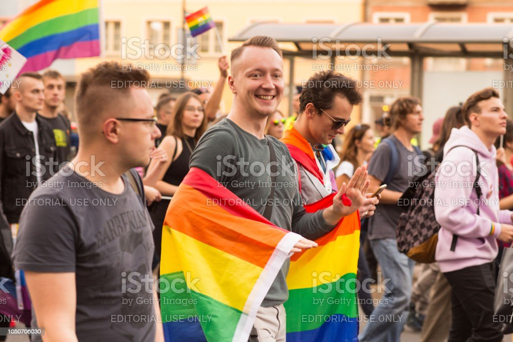 Happy young adult wrapped in LGBT flag stock photo