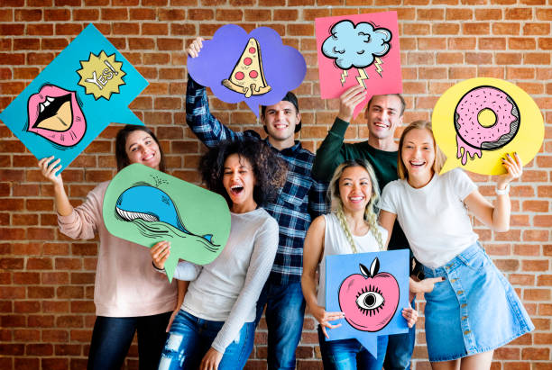 Happy young adults holding thought bubbles with pop art fashion icons youth culture concept stock photo