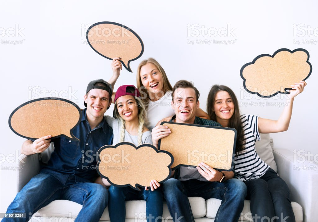 Happy young adults holding up copy-space placard thought bubbles stock photo