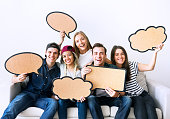 Happy young adults holding up copy-space placard thought bubbles