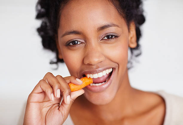 Happy young African American female eating a carrot stock photo