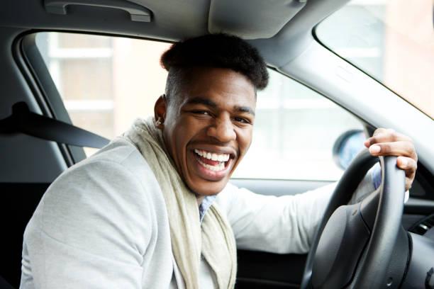 Glücklicher junger afrikanischer Amerikaner sitzt im Auto und lacht – Foto
