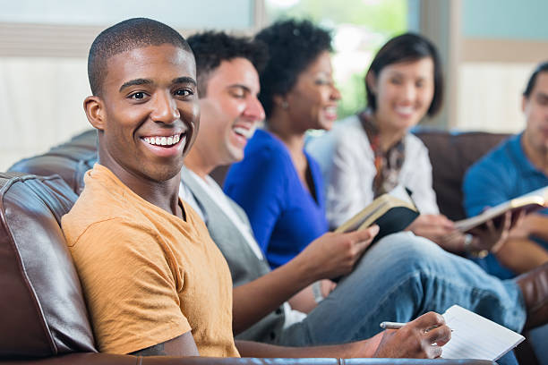 Happy young African American man taking notes duirng Bible study stock photo