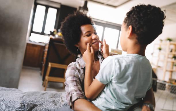 Glückliche junge afrikanische amerikanische Mutter, die Spaß mit ihrem Kind hat – Foto