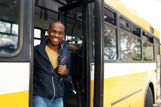 glücklich junge afrikanische amerikanische ReiseMann mit Tasche aus Bus – Foto