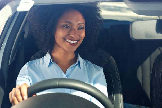glückliche junge afroamerikanische Frau Autofahren und lächelnd – Foto