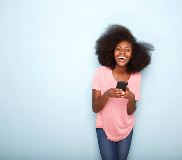 happy young african american woman holding smart phone Portrait of happy young african american woman holding smart phone afro caribbean ethnicity stock pictures, royalty-free photos & images