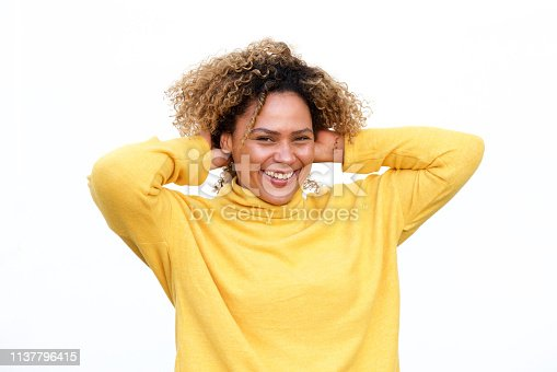 910856488 istock photo happy young african american woman laughing against white background with arms behind head 1137796415