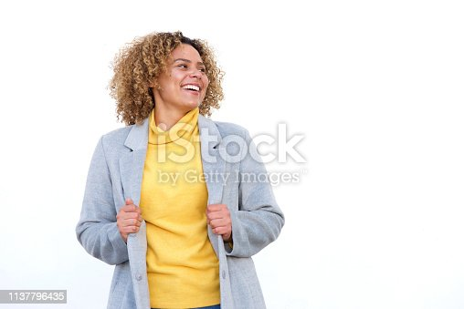 910856488 istock photo happy young african american woman laughing against white background with coat 1137796435