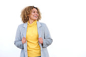 istock happy young african american woman laughing against white background with coat 1137796435