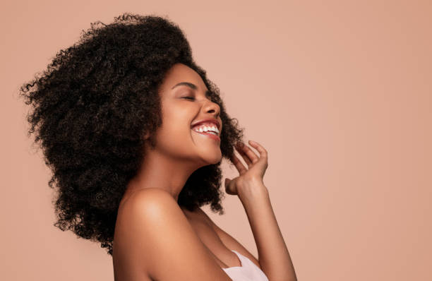 Happy young African American woman on pink background stock photo