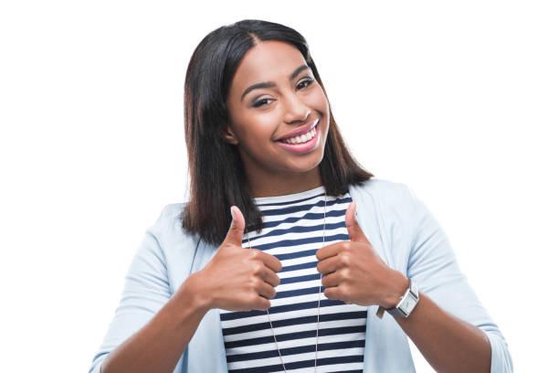 Heureuse jeune femme afro-américaine montrant les pouces vers le haut et souriant à la caméra - Photo