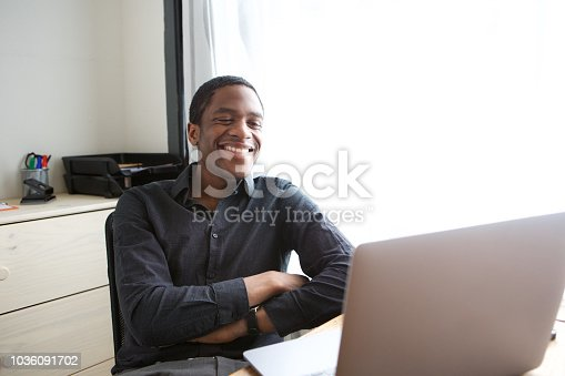 istock happy young african businessman sitting at desk with laptop computer 1036091702