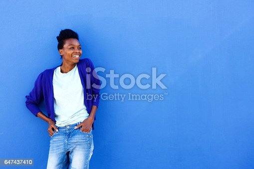 istock Happy young african female standing against blue wall 647437410