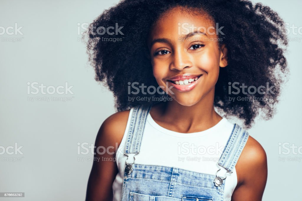 Happy young African girl standing against a gray background stock photo