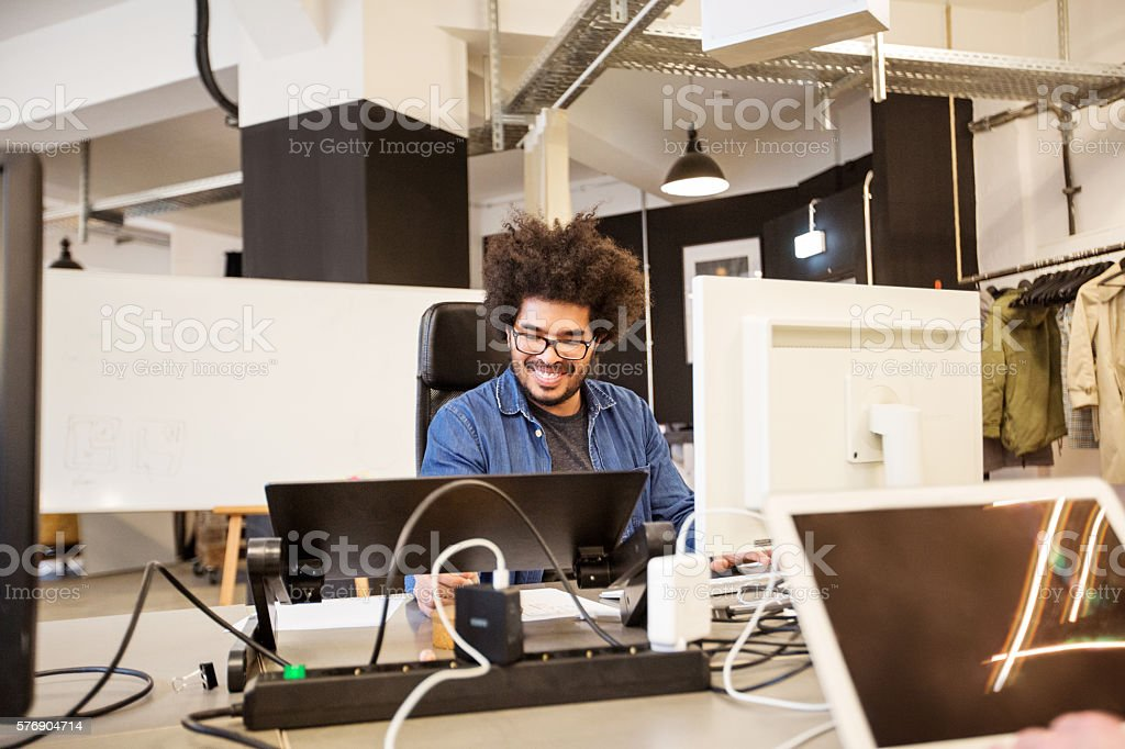 Happy young african male designer working stock photo