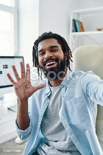 Happy young African man smiling and looking at camera while taking selfie indoors