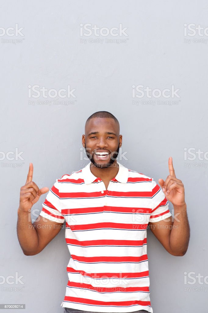 happy young african man pointing up against gray wall stock photo