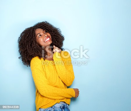 istock happy young african woman looking up on blue background 992844338
