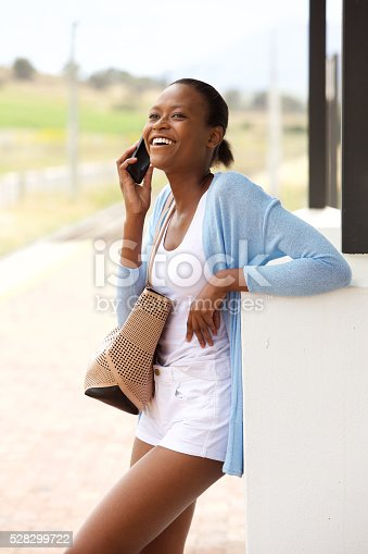 862201618 istock photo Happy young african woman with bag talking on mobile phone 528299722