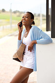 istock Happy young african woman with bag talking on mobile phone 528299722