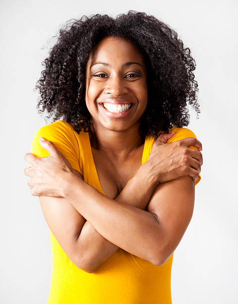 happy young African-American woman hugging herself stock photo