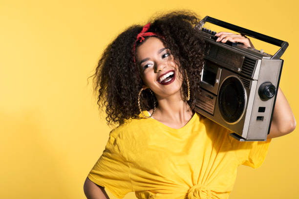 Happy young afro woman holding boombox stock photo