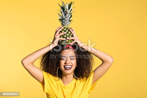 istock Happy young afro woman holding pineapple on head 688996942