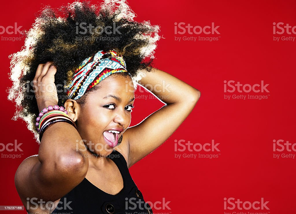 Happy young afro-haired cutie gets in the groove royalty-free stock photo