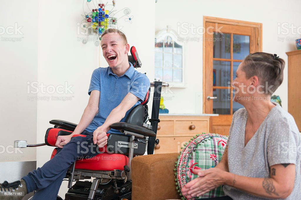 Happy young ALS patient with his mom stock photo