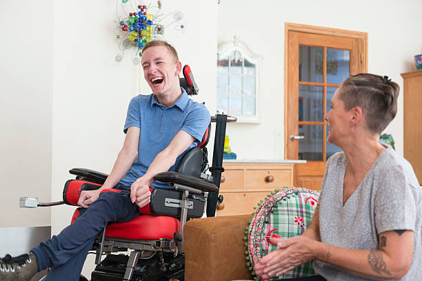 Happy young ALS patient with his mom Color image of a real life young physically impaired ALS patient spending time with his mother at home. He is happy. amyotrophic lateral sclerosis stock pictures, royalty-free photos & images