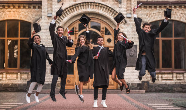 Happy young alumni Successful graduates in academic dresses are holding diplomas, looking at camera and smiling while jumping for the photo outdoors alumnus stock pictures, royalty-free photos & images