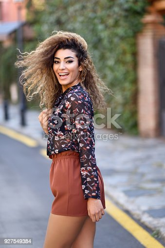 istock Happy young arabic woman with black curly hairstyle. 927549384