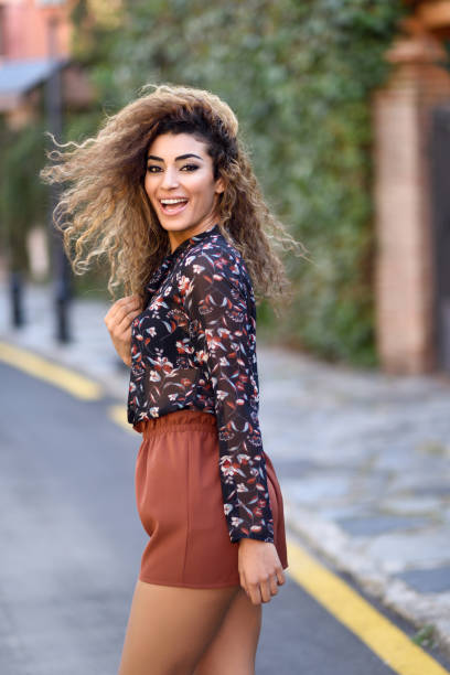 Happy young arabic woman with black curly hairstyle. Happy young arabic woman with black curly hairstyle. Arab girl smiling in the street moving her hair. shorts stock pictures, royalty-free photos & images