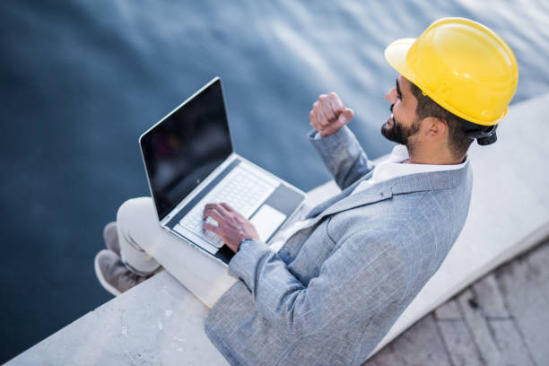 Happy young architect using laptop on a commercial dock. stock photo