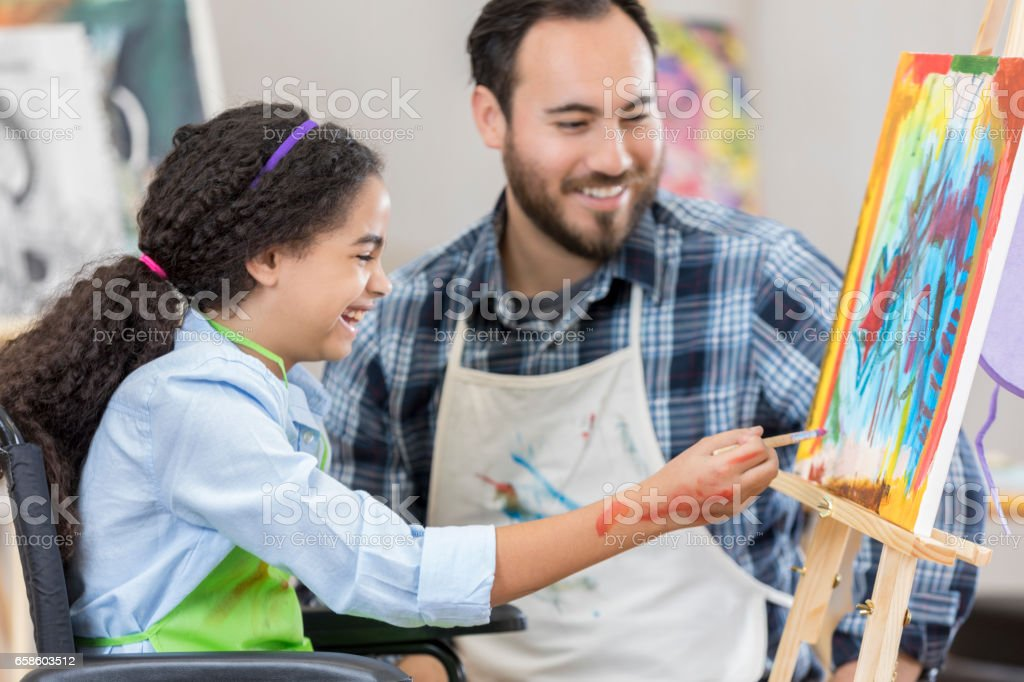Happy young artist in wheelchair stock photo