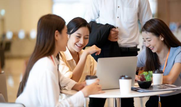 クリエイティブプロジェクトについて議論する幸せなアジアのビジネスの人々は、オンラインマーケティングに関する現代のクリエイティブオフィスディスカッションでラップトップとのミ� - 談笑する ストックフォトと画像