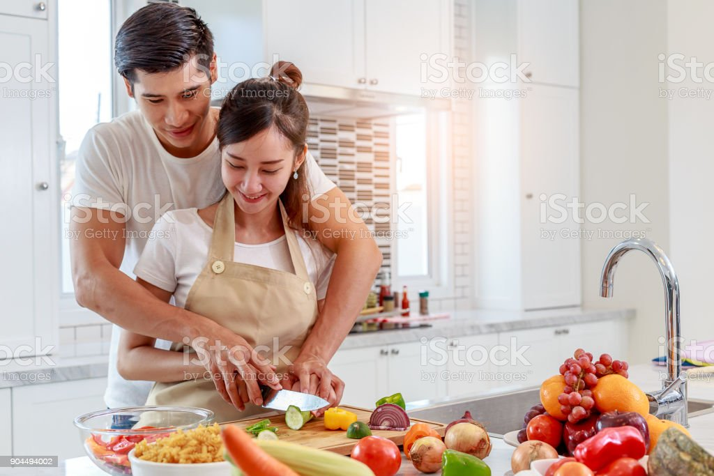Happy young Asian couple cooking healthy food together in the kitchen at home stock photo