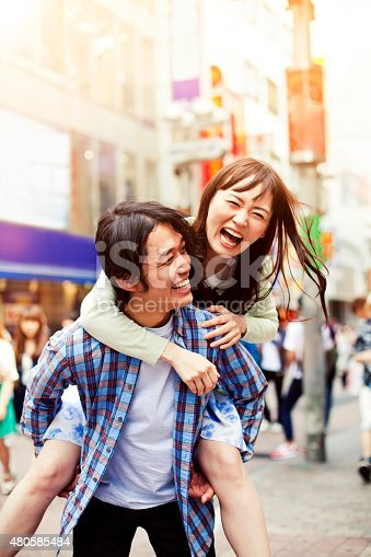 istock Happy young asian couple having fun with piggy back 480585484