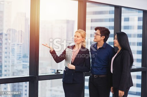 955988522istockphoto Happy young Asian couple meeting with Female Real Estate and lawyer agent show view of new house 1179019441