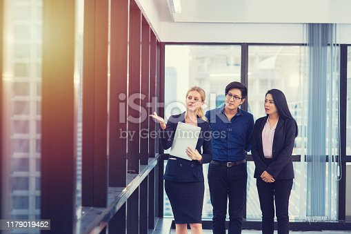 955988522istockphoto Happy young Asian couple meeting with Female Real Estate and lawyer agent show view of new house 1179019452
